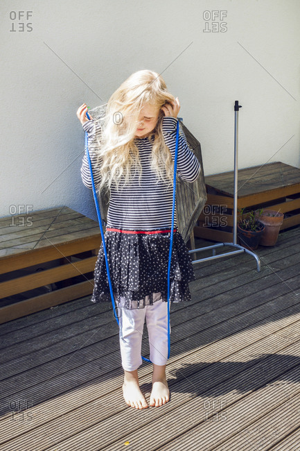 Berlin, Germany - May 30, 2015: Young blonde girl playing outside with a jump rope