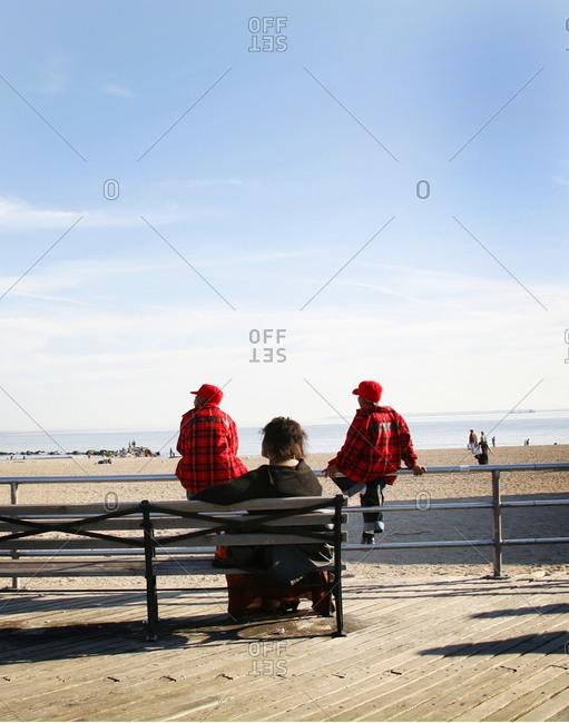 People sitting on the boardwalk on a winter day in Coney Island, Brooklyn, New York