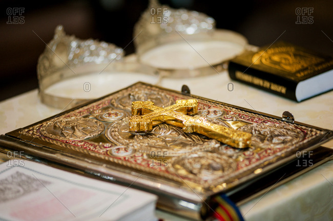 Golden crucifix on closed Bible with silver crowns for religious marriage in the background