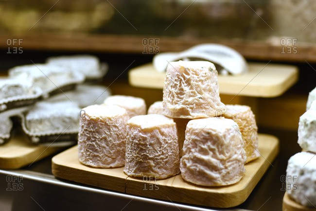 Many small wheels of cheese displayed on a wooden board