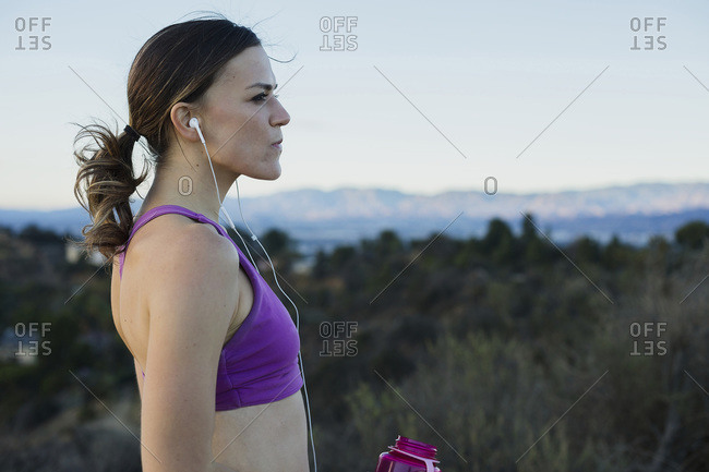 Athletic woman with earbuds and bottle