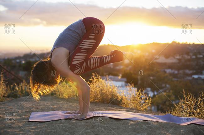 Woman on hill doing yoga pose