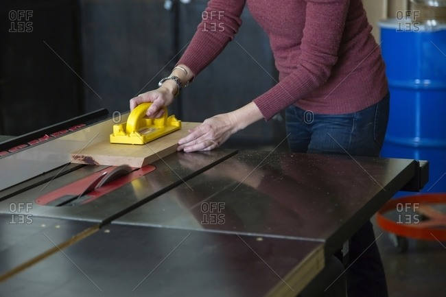 Woman cutting a board with saw