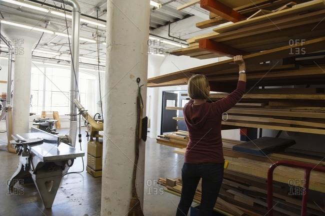 Woman selecting board in workshop