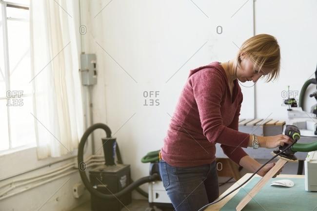 Woman sanding a board in workshop