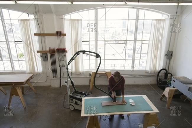 Woman sanding board in workshop