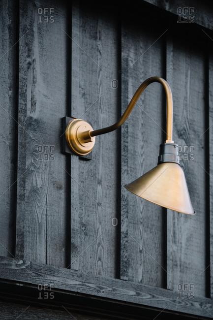 Detail of a brass gooseneck light on an outdoor wood structure