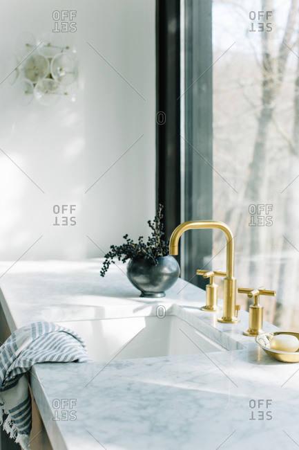 Kitchen sink with gold faucet against a large picture window