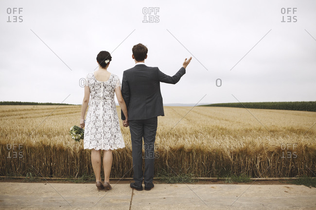 A bride and a groom in a wheat field
