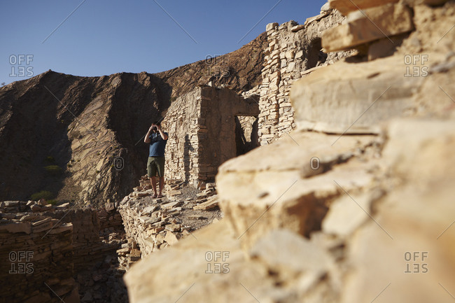A man takes a photo from the ruins of Birkat Al Mouz village