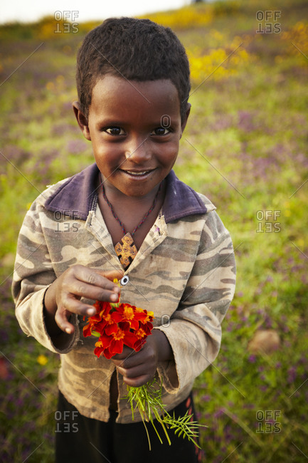Ethiopian boy with flowers in a meadow