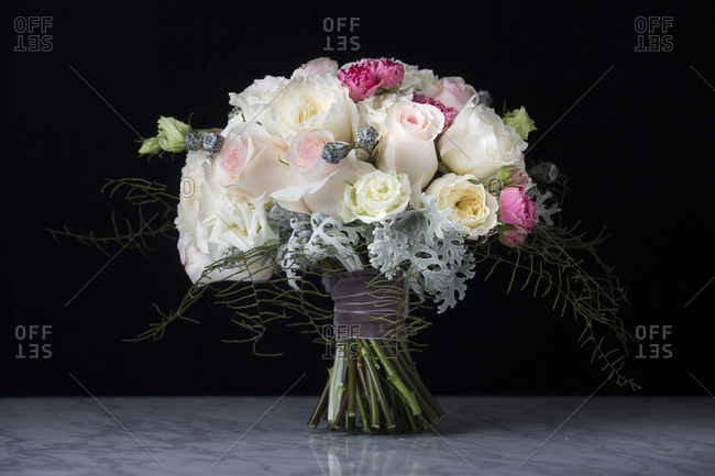 A bouquet of flowers on a table in front of a black background