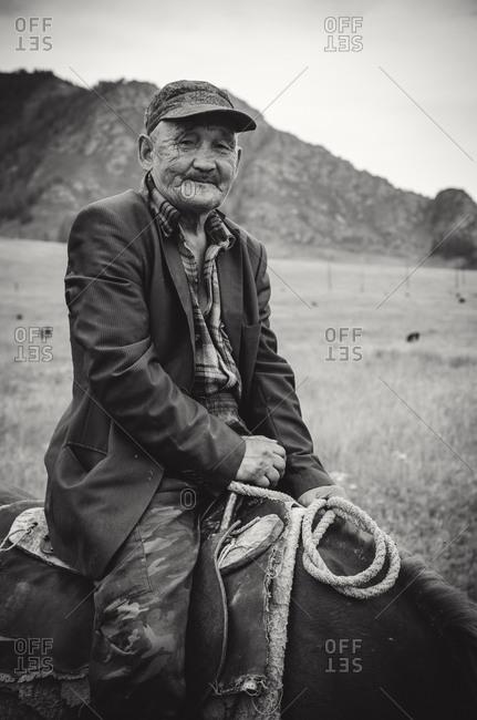 Kyrgyzstan - August 15, 2014: Elderly man on horse in Kyrgyzstan