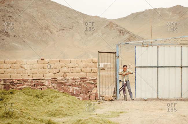 Mongolia - August 17, 2014: Smiling boy with bicycle at gate in Mongolia
