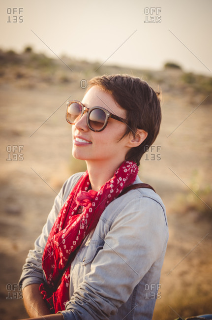 Rajasthan, India - November 10, 2014: Young female tourist in sunglasses in desert landscape at dusk