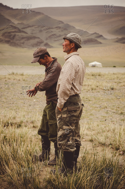 Mongolia - August 17, 2014: Two Mongolian men talking together in field