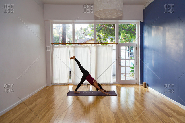 Woman in a yoga studio in a one legged downward-facing dog pose