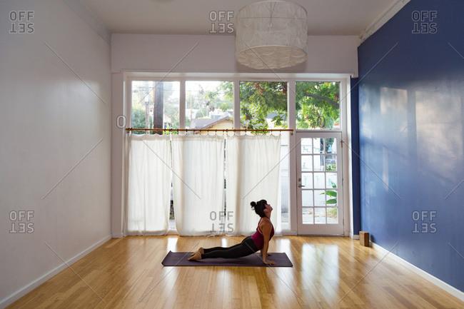 Woman in a yoga studio in an upward facing dog pose