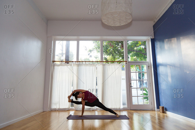 Woman in a yoga studio in a monkey side plank pose