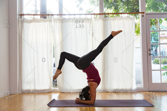 Woman in a yoga studio in a headstand pose