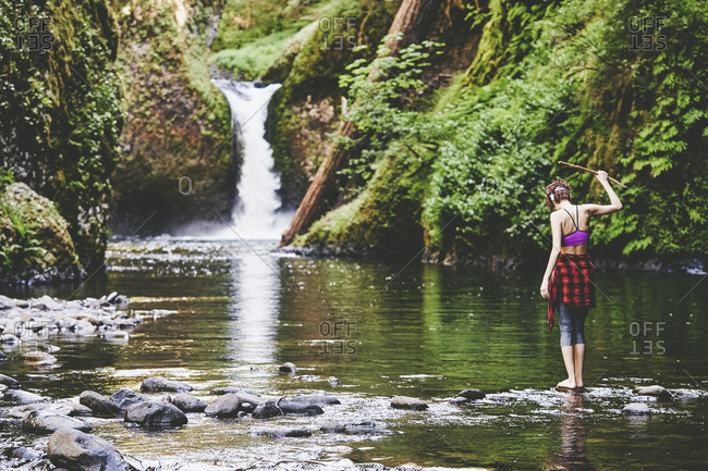 Woman standing in Eagle Creek at the base of Punchbowl Falls, Oregon