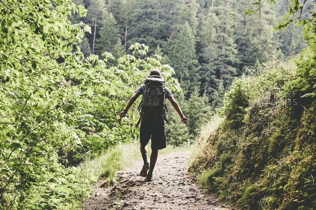 Man backpacking along a narrow trail near Punchbowl Falls in Oregon