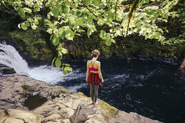Woman standing on a rocky outcropping overlooking Punchbowl Falls in Oregon