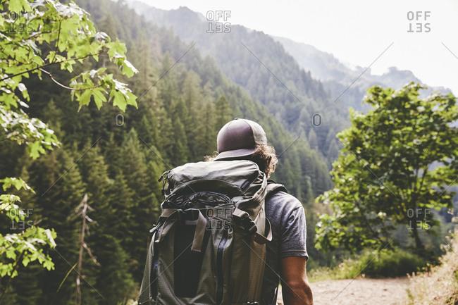 Man backpacking along a narrow trail near Punchbowl Falls in Oregon
