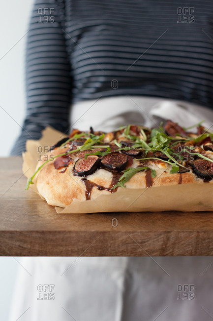 Person holding a flatbread pizza on a cutting board