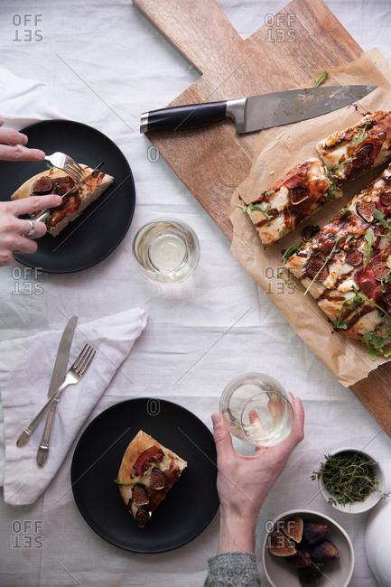 Two people enjoying a flatbread pizza
