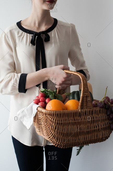 Woman holding a basket filled with fruits and vegetables