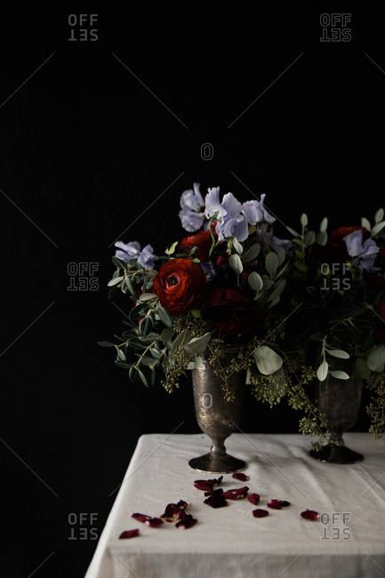 Still life with vases holding roses and purple flowers beside rose petals on a white tablecloth