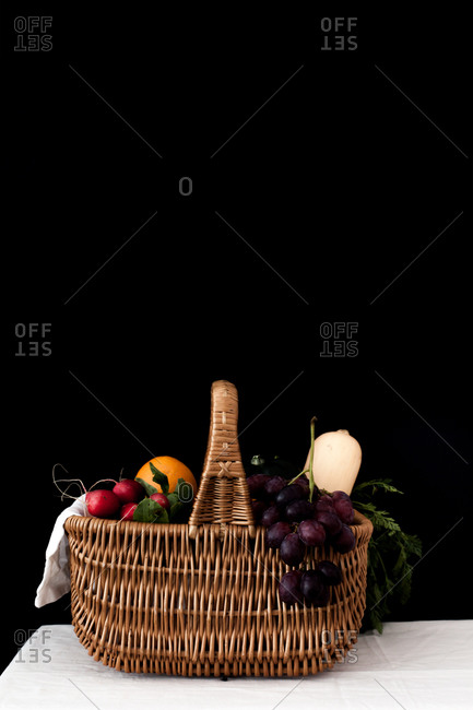 Side view of a basket filled with fruits and vegetables on a table