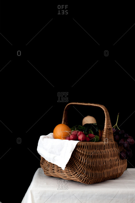 Still life with a basket filled with fruits and vegetables on a table