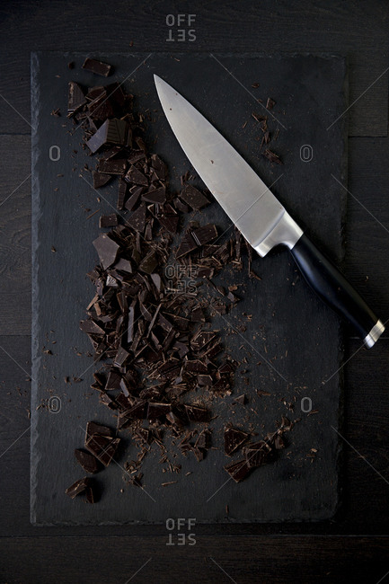 Pieces of baking chocolate on a cutting board with a knife