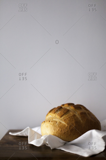Round loaf of bread on a white cloth on a table