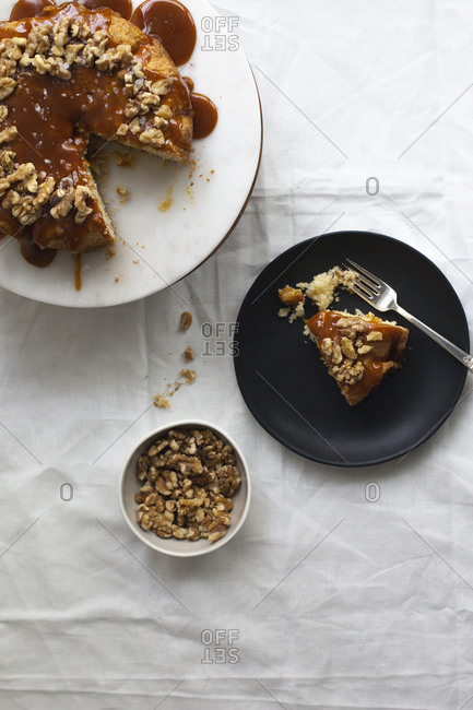 Caramel covered cake beside a cut slice and a bowl of walnuts