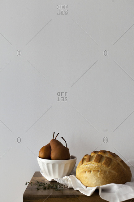 Round loaf of bread alongside a bowl of pears on a table