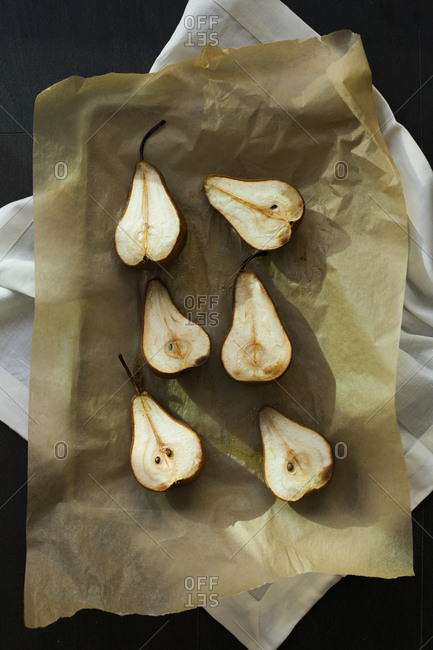Sliced pears arranged on a baking pan lined with parchment paper
