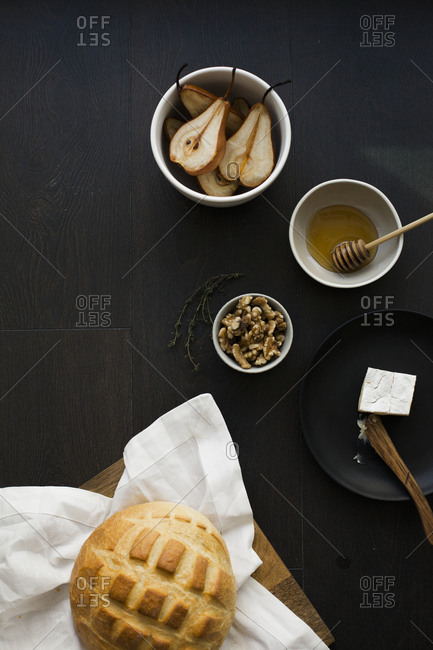 Round loaf of bread with bowls of baked pears, honey, cheese, and walnuts