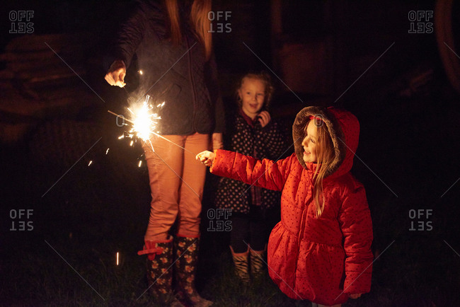 Side view of girl wearing red fur trim coat holding sparkler being ignited by mother, smiling