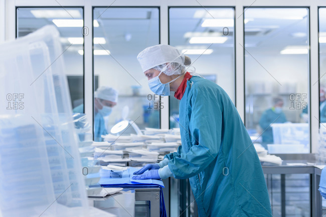 Worker inspecting surgical instruments in clean room of surgical instruments factory