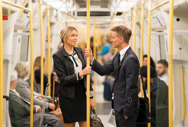 Businessman and businesswoman talking in mass transit