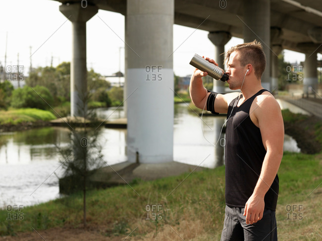 Young man beside river drinking from water bottle