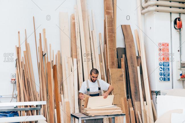 Carpenter selecting wood in workshop