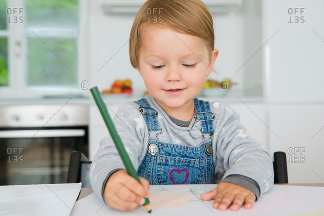 Female toddler drawing at kitchen table