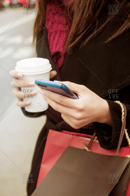 Close up of woman using cell phone while drinking coffee on the go