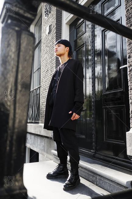 Young man standing in front of a black door