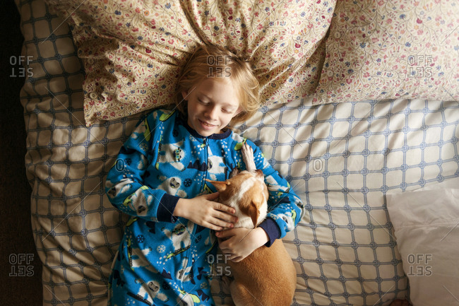 Boy cuddling in bed with his dog
