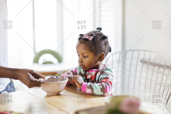 Parent feeding daughter spoonful of cereal